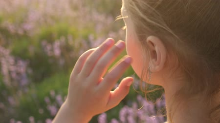 close-up of young girl hand correcting hairstyle outdoors
