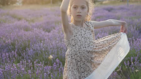 cute little girl merrily dances with a smile on her face among fields of lavender