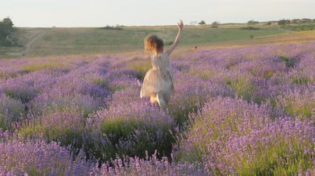 cute little girl merrily flees and happily jumping among lavender field