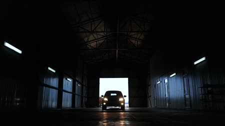 electromotor : car silhouette headlight glow front view. automobile arrive service station. large garage. machine drives into for diagnosis Stock Footage