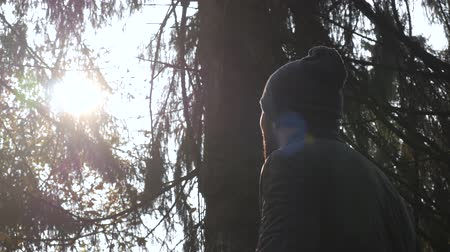 close-up bearded man. view outdoor nature at sunset. Guy outerwear hat autumn season. scene silhouette man. looking at the sun. bright light. travel in forest.