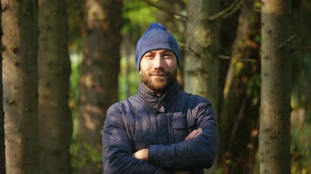 Portrait of a handsome man standing in an outerwear and knitted hat. Happy smiling young guy. nature background Wideo