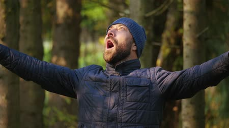 slow motion. Close-up traveler adult bearded man in a jacket and knitted hat. emotion brutal guy loudly screaming raising her hands up standing outdoors in nature