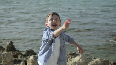 enjoyable : close up happy small boy control flying colorful kite on the beach, background of the sea summertime