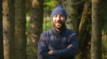 угождать : Portrait of a happy smiling and smiling man. outerwear and knitted hat. nature background. slow motion Стоковые видеозаписи
