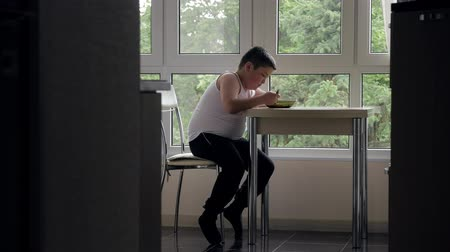 repast : fat little boy sits in the kitchen at the table, eats soup on the background of the window Stock Footage