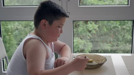 repast : little fat boy sitting near the window and eats delicious soup. concept childhood obesity