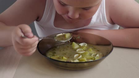 repast : fat Kid boy with appetite eats soup in the kitchen, concept obese children. closeup