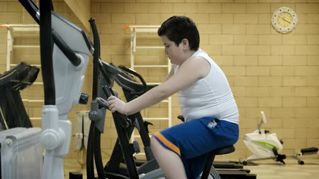 minor : fat little boy workout exercise bike in fitness room. weight loss concept Stock Footage
