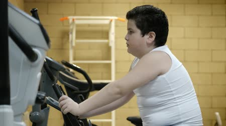 упитанность : obesity little boy training bike in gym. losing weight concept