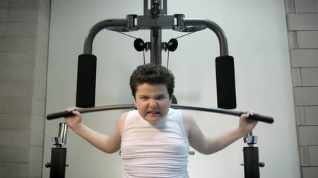 интенсивность : thick angry kid boy trains in gym fat burning.