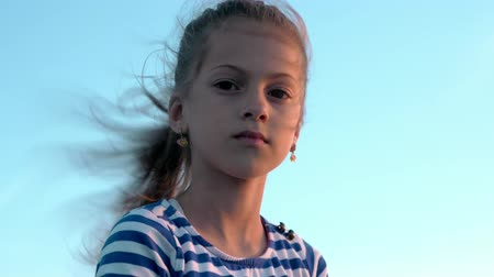 zarmoucený : portrait of attractive little girl in striped shirt on sky background with developing hair at sunset
