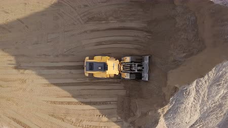 buldozer : Aerial view loading bulldozer in open air quarry.