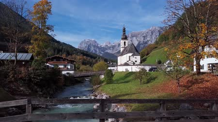 Бавария : Flight over footbridge near famous Parish church St. Sebastian, in Ramsau, Berchtesgaden, Bavarian Alps Germany.