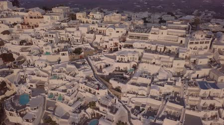 エーゲ : Flight over traditional terraced white villas in Fira town at sunset, Santorini, Greece. Original untouched LOG format.