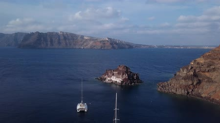 УВР : Flight over small island church (Nisis Agios Nikolaos) near Oia town, Santorini island, Greece Стоковые видеозаписи