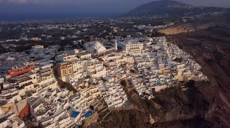 кратер : Flight over of Fira (Thira) town at sunset, Santorini island, Greece