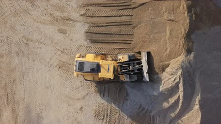 lom : Aerial view loading bulldozer in open air quarry.