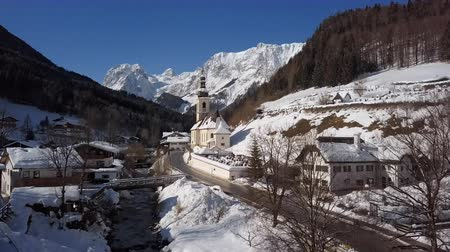 chapel : Winter flight over footbridge near famous Parish church St. Sebastian, in Ramsau, Berchtesgaden, Bavarian Alps Germany.