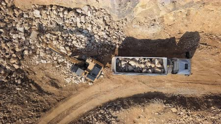 Top aerial view of excavator loading stones into dump truck in open air quarry.