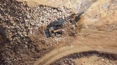 Top aerial view of excavator loading stones in open air quarry.