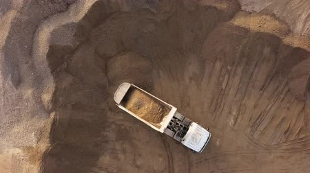 Top aerial view of dump truck unloading sand in open air quarry.