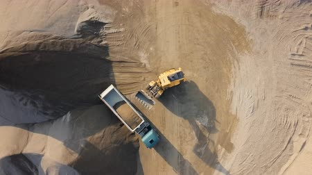 Top aerial time lapse of bulldozer loading stones into empty dump truck in open air quarry. Stok Video