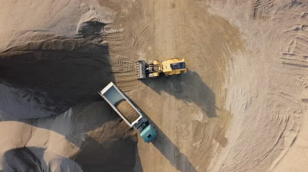 Top aerial view of bulldozer loading stones into empty dump truck in open air quarry. Stok Video
