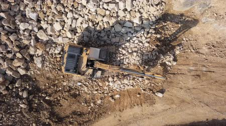 buldozer : Top aerial view of excavator loading stones in open air quarry.