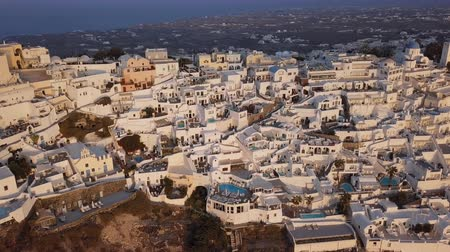 Flight over traditional terraced white villas in Fira (Thira) town at sunset, Santorini, Greece Stok Video