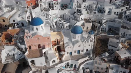УВР : Top aerial view of Three Blue Domes church in Oia town on Santorini island, Greece Стоковые видеозаписи