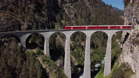 Aerial panorama of Swiss red train on famous Landwasser Viaduct (Landwasserviadukt), Graubunden, Switzerland. Stok Video
