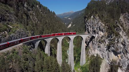 Aerial panorama of Swiss red train on famous Landwasser Viaduct (Landwasserviadukt), Graubunden, Switzerland. Vídeos