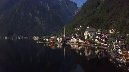Flight around Hallstatt village over calm Hallstatter See at sunny summer morning, in Salzkammergut, Upper Austria.