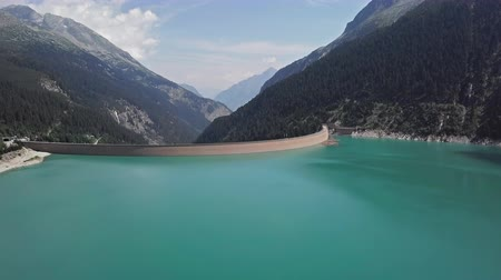 Flight over of Schlegeis Stausee reservoir dam and panoramic Alpine Road in the Zillertal Alps, Tirol, Austria.