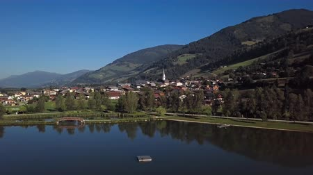 Flight around of Uttendorf town over calm lake at sunny summer morning, in Land Salzburg, Austria.