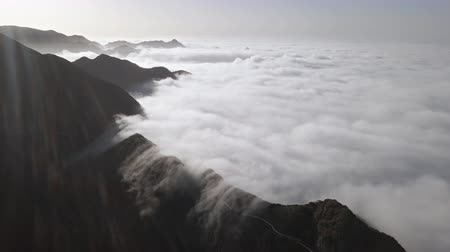 falésias : Aerial view of clouds running over mountain road in Anaga mountain range, Tenerife, Canary islands, Spain.
