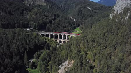 выражать : Aerial view of red train rides on famous Kalte Rinne Viaduct on historical Semmering mountain railway (Semmeringbahn), Lower Austria.