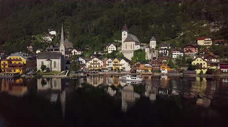 часовня : Aerial view of boat arrive in Hallstatt village over calm Hallstatter See at sunny summer morning, in Salzkammergut, Upper Austria. Стоковые видеозаписи
