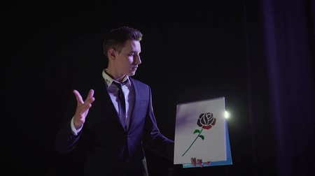 handkerchief : A magician shows a trick with a painted flower. The magician changes the color of the drawn picture. Magician with painted rose.