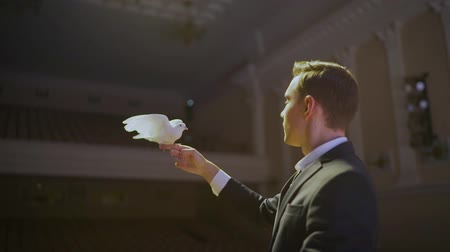 mendil : Magician releases dove from hands, slow motion. Magician with a dove.