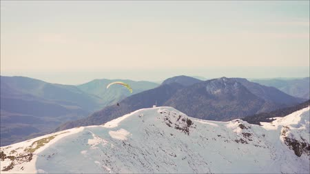 szybowiec : Sportsman on red paraglider soaring over the snowy mountain peaks. Paraglider on the background of snowy mountains.