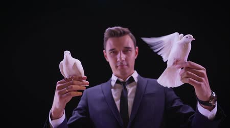 ptak : Magician with pigeons. Shows focus with two white pigeons. Magician releases dove from hands, slow motion