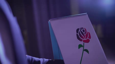 coque : Trick with a painted rose that changes color. The painted rose turns red. Magician show trick and photo shoot in studio Stock Footage