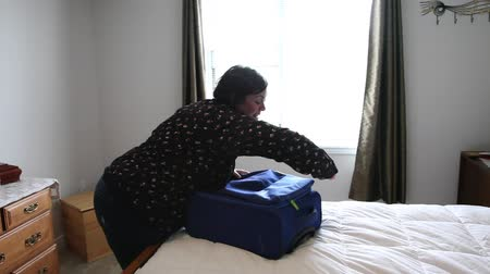 vigyorgó : Getting ready to go away on a trip, a woman happily closes up her suitcase