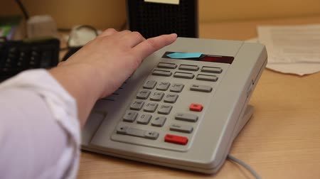 A hand places a telephone back on its cradle or reciever