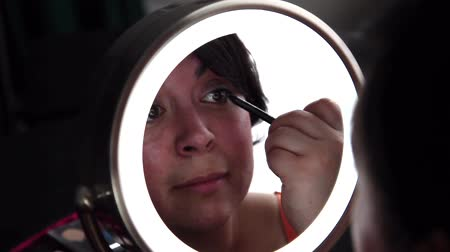 határozza meg : A gorgeous dark haired woman puts on eye liner as part of getting ready routine