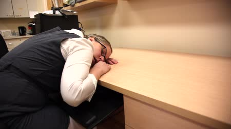 Woman takes a nap on her desk at work