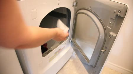 lids : A hand opens the door to the clothes dryer and inserts a sheet of softener before closing the door