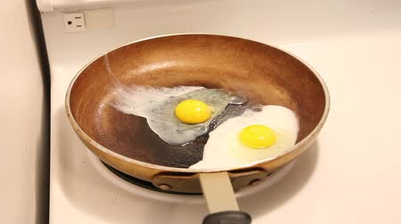 Hand cracks an egg into a skillet with another egg and then both eggs fry and steam nicely.
